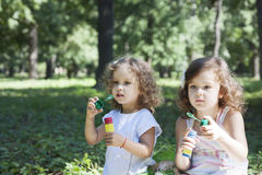 Children and soap bubbles. Little girls blowing soap bubbles in the park royalty free stock photography