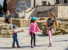 Children and soap bubbles. Lublin. Poland 2018 - April 14. Old Town, children are played with big soap bubbles royalty free stock photos