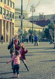 Children with Soap Bubbles on The Street. Prague,Czech Republic - October 16, 2016 : Children Jumping Up to Burst Big Soap Bubbles stock images