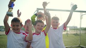 Soccer players wave hands holding trophy by gate