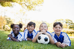children soccer team smiling at camera while lying on the floor Stock Images