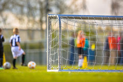 Children soccer training. Modern aluminum soccer goal for youth with training children in the background Stock Photo