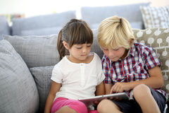 Children on sofa playing games with tablet Stock Photos