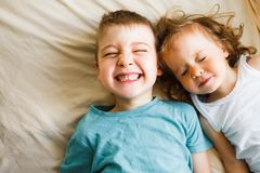 Children in soft warm pajamas playing in bed. Little children in soft warm pajamas play in bed, laugh and tumble Royalty Free Stock Image