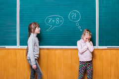 Children solve math problem. One girl, standing at the school board, assigns a mathematical task to another girl who can not solve it stock image