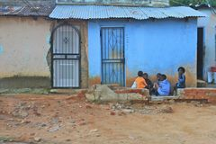 Children of South Africa. South African children circled in the dust next to bright blue building Stock Photos