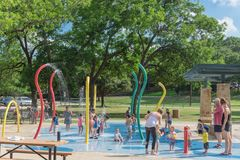 Children splash pad or spray ground Parr Park, Grapevine, Texas, USA. GRAPEVINE, TX, US-May 28, 2018:Diverse kids enjoy water splash pad or sprayground at Parr royalty free stock photo