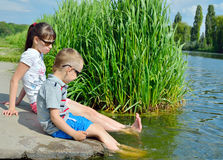 Children splash their feet in the water of the lake. Active outdoor recreation. Friendship brother and sister. Happy childhood Stock Photography