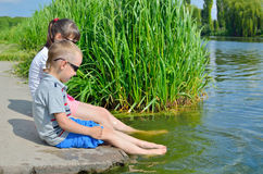 Children splash their feet in the water of the lake. Active outdoor recreation. Friendship brother and sister. Happy childhood Royalty Free Stock Photo