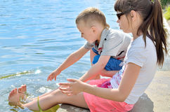 Children splash their feet in the water of the lake. Active outdoor recreation. Friendship brother and sister. Happy childhood Stock Image