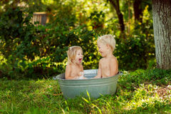 Children splash in the water. Boy and girl swimming in a bowl royalty free stock photography