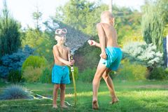 Two brothers play on a summer hot day in the garden. Children are splashing with a garden hose. royalty free stock photo