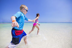 Children splashing in the ocean on a tropical beach vacation Stock Image