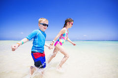 Children splashing in the ocean on a tropical beach vacation Royalty Free Stock Photos