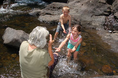 Children splashing water on their grandmother. Two children splashing water on their grandmother in a country brook Royalty Free Stock Photography