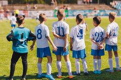 Children Sport Team Photo. Group of Young Boys Playing Soccer Tournament Match. Football Soccer Game For Children. Kids Soccer Players Standing Back on Bench stock photography