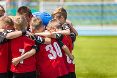 Children sports soccer team. Kids standing together on the football pitch. Soccer coach motivational team talk. Youth football soccer coach motivating players Royalty Free Stock Photography