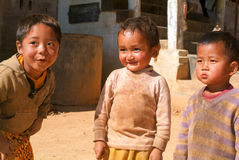 Children stand barefoot outside their family house at the villag Royalty Free Stock Image