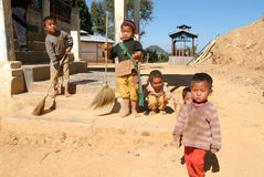 Children stand barefoot outside their family house at the villag Royalty Free Stock Photo