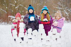 Children stand behind snow wall holding snow blocks Royalty Free Stock Images