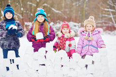 Children stand behind wall made from snow bricks Royalty Free Stock Photography