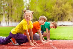 Children stand with bended knee ready to run. Children in colorful uniforms stand with bended knee ready to run the marathon together on the stadium Stock Images