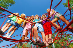Children stand close on ropes of playground net Royalty Free Stock Photos
