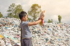 Children stand looking at the dolls collected from the garbage,. The lives and lifestyles of the poor, The concept of child labor and trafficking stock photos