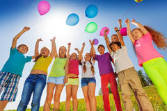 Children stand in semi-circle with balloons up Stock Images