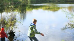 Children stand on the shore of the pond and throw stones. Walks in the fresh air. Children stand on the shore of the pond and throw stones stock video