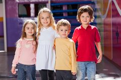 Children Standing Arms Around In Kindergarten. Portrait of cute preschool children standing arms around in kindergarten Stock Image