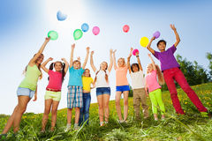 Children standing with arms up to flying balloons Stock Images