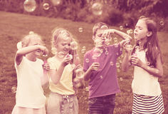 Children standing and blowing bubbles. Children in elementary school age standing on green grass and blowing bubbles Royalty Free Stock Photography