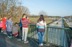 Children standing on the bridge above the autobahn and photographing cars stock images