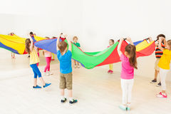 Children standing in circle and waving parachute Royalty Free Stock Photos