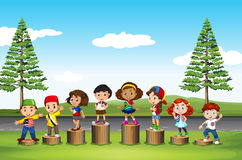 Children standing on logs in the park Royalty Free Stock Images