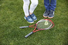 Children standing near badminton racquets and shuttlecock on green grass. Cropped view of children standing near badminton racquets and shuttlecock on green royalty free stock photography