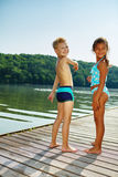 Children standing on a pier at the lake Stock Photography
