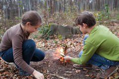 Children starting a campfire Royalty Free Stock Image