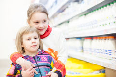 Children in   store at   shelves with products. Royalty Free Stock Photo