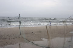 Children on a stormy Beach. Children playing with their feet in the water on a beach in Poland. Fishing nets visible in the foreground. A stormy and cold morning Stock Photo