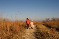 Children Strolling Down The Path. Two young children walking hand in hand down a path in the Kansas Flint hills Royalty Free Stock Photo
