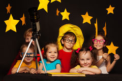 Children studying astronomy with telescope. Six happy kids, boys and girls sitting at the table and studying astronomy with a telescope royalty free stock images