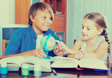 Children studying with books indoors. Teenage boy and younger sister studying with books indoors Stock Photography