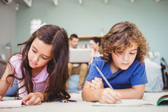 Children studying while parents in background Royalty Free Stock Photography