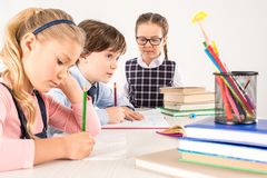Children studying together and writing. In notebooks royalty free stock photo