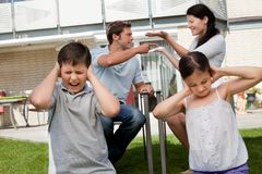 Children suffers while parents fight in background Royalty Free Stock Photos