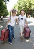 Children with suitcase run.