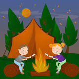 Children Summer Camp. Boy and Girl sitting by Fireplace. Bonfire with Marshmallow. Stock Photos