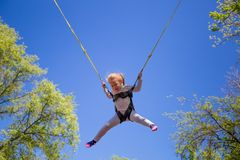 Children summer entertainment. Little girl jumping on children t Royalty Free Stock Photos